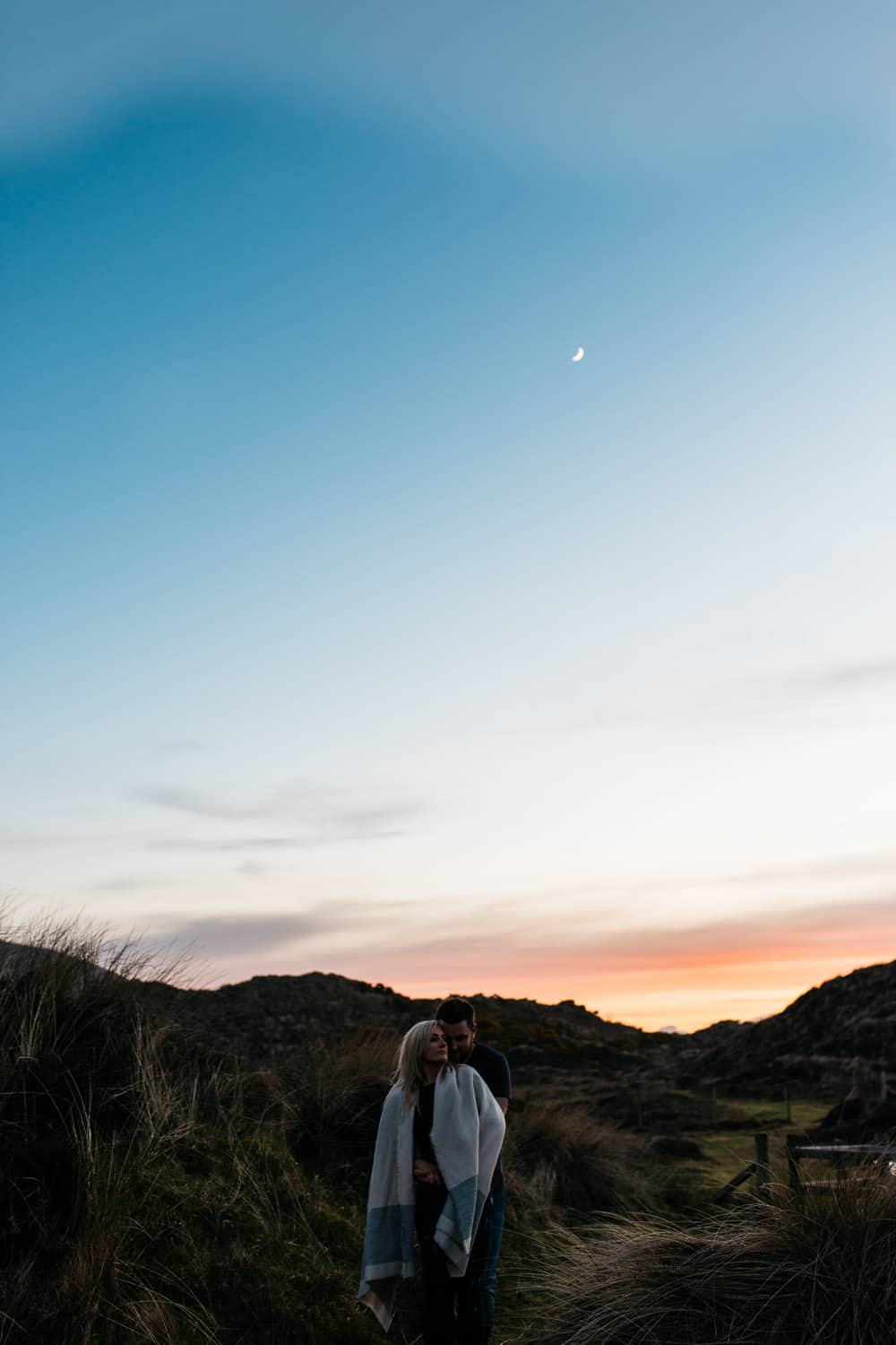 couple hugging at sunset with moon Engagement Photography Belfast
