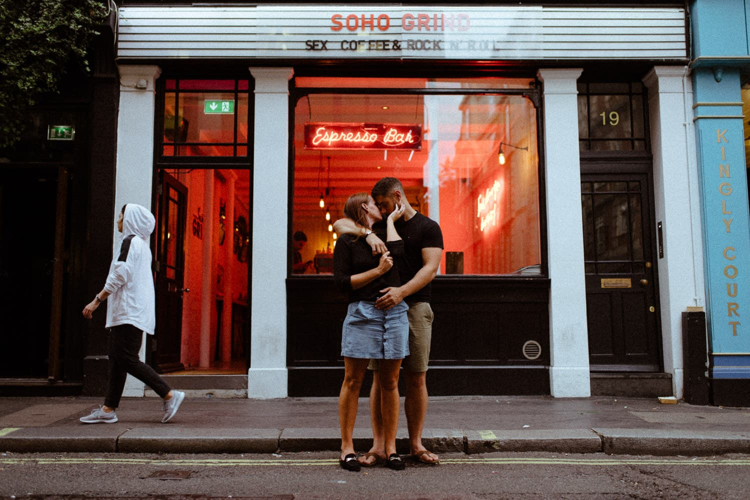 couple in an embrace outside coffee shop London Engagement Photography Soho