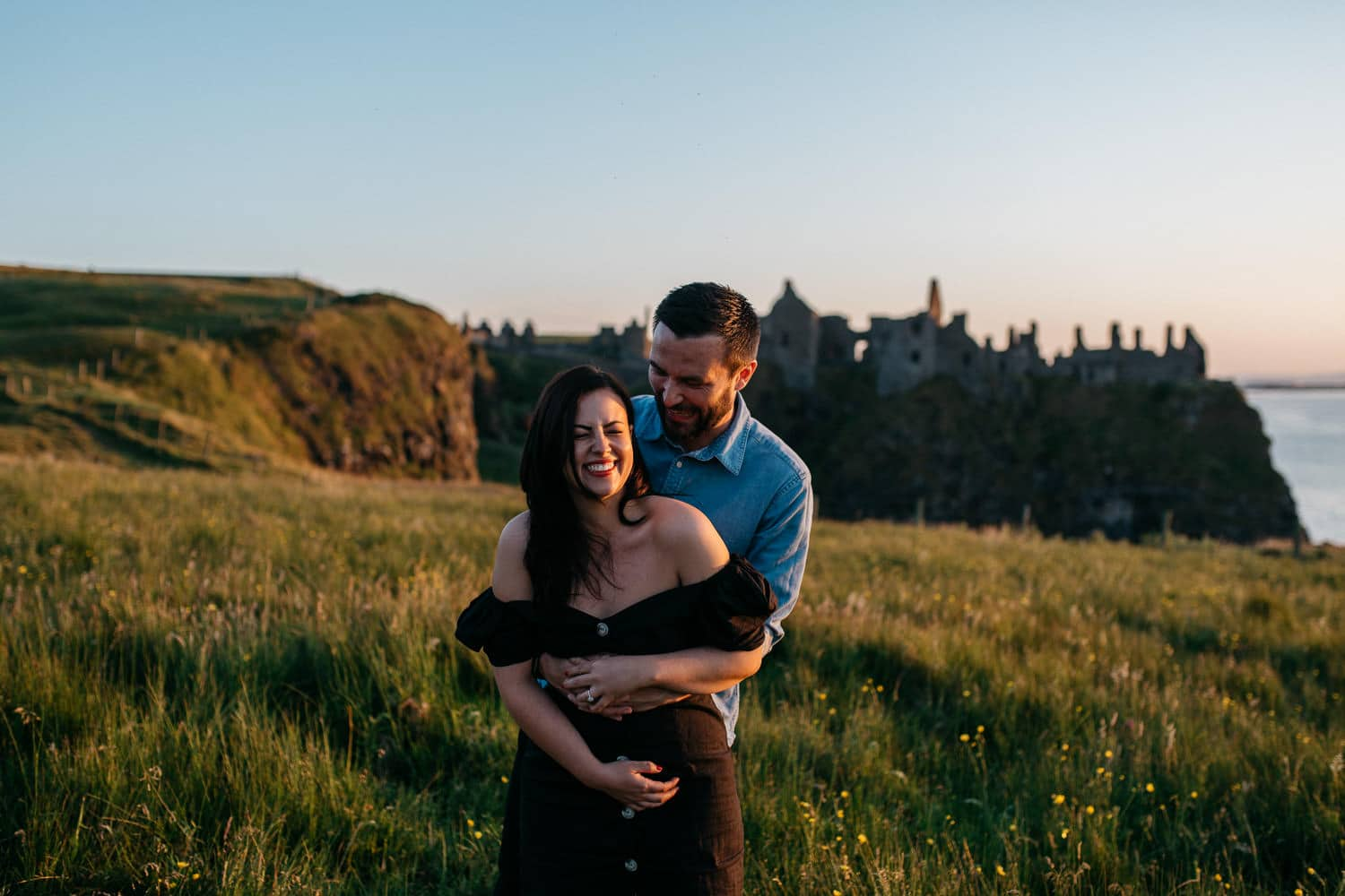 couple laughing in from of Dunluce Castle Engagement Photography Northern Ireland