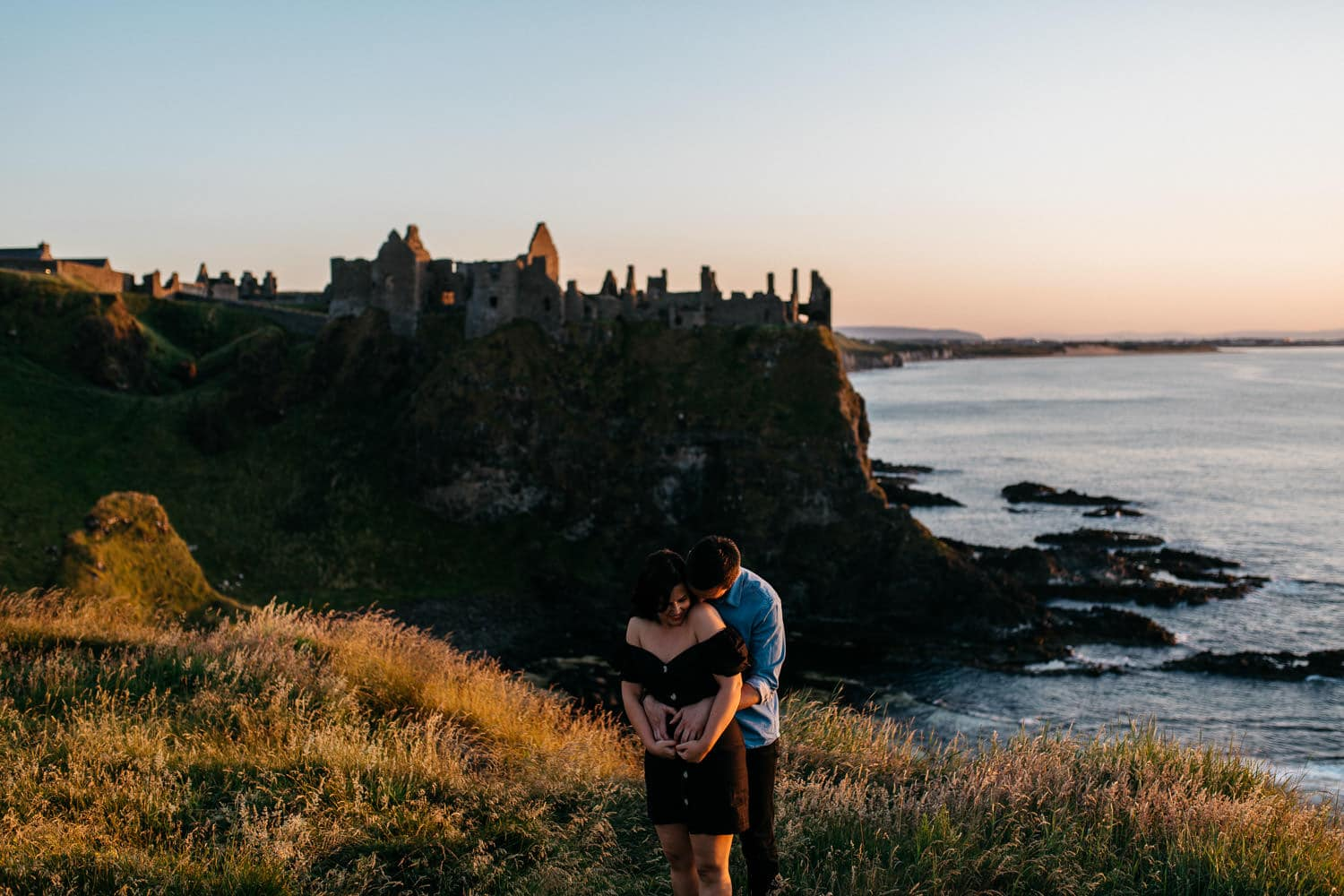 couple hugging in from of Dunluce Castle Engagement Photos Northern Ireland