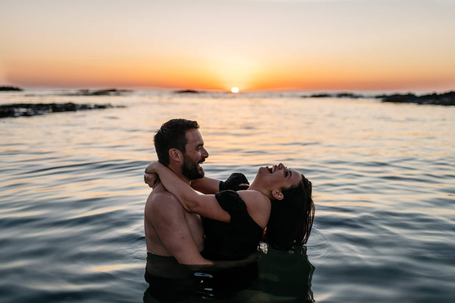 couple laughing in the water at sunset Engagement Photos Northern Ireland
