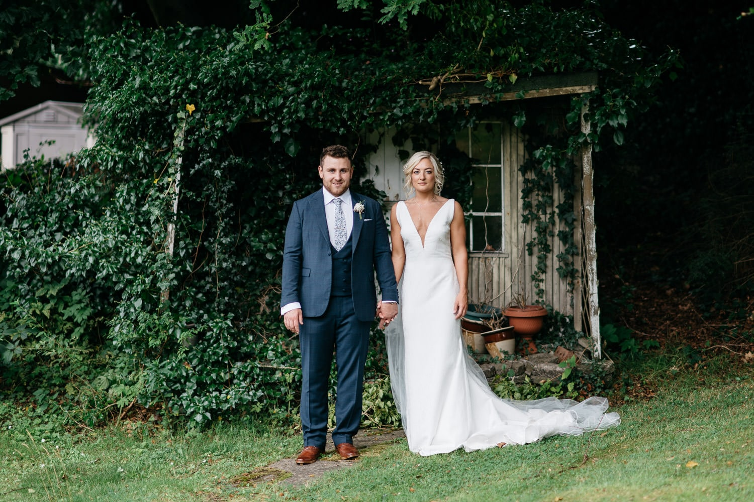bride and groom holding hands in garden in front of rustic shed Wedding Photographer Northern Ireland