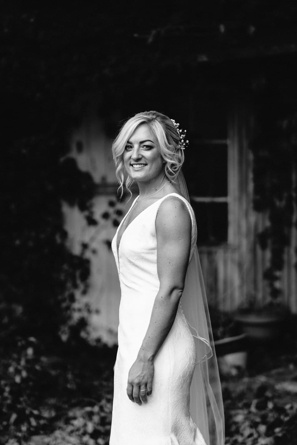 bride standing in garden black and white