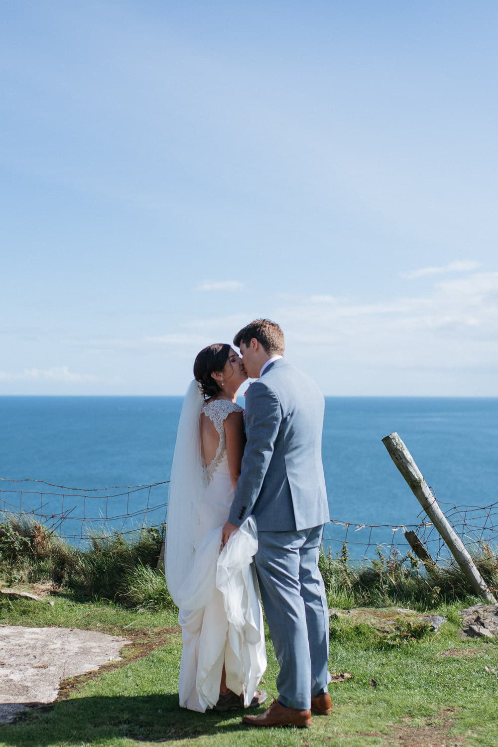 bride and groom kissing on cliff top