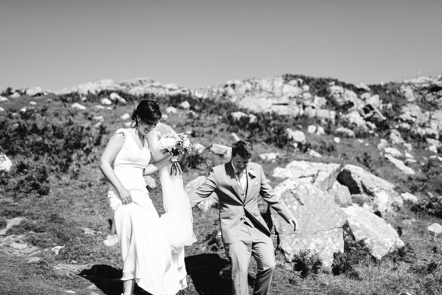 bride and groom walking down from the cliffs Lissanoure Castle Wedding Photography