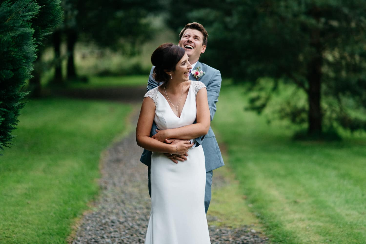 bride and groom laughing down the lane Lissanoure Castle Wedding Photography