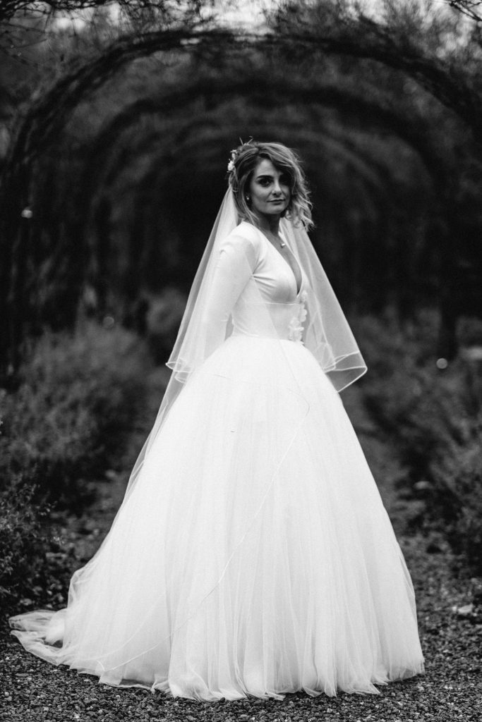 black and white of bride standing in archway Larchfield Estate Wedding