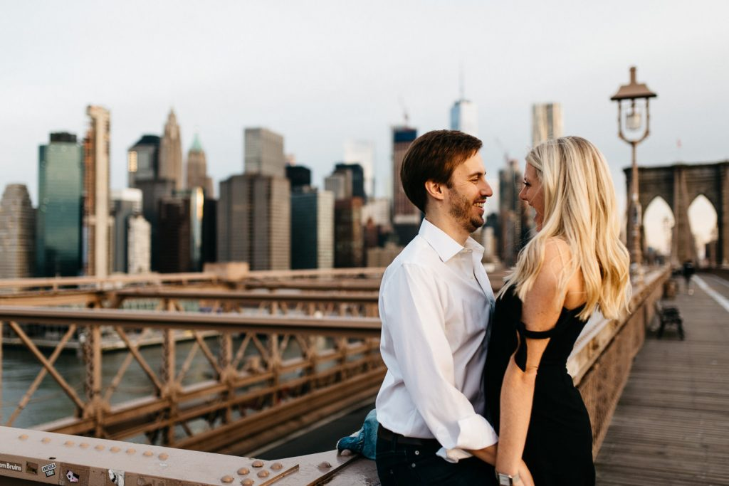 couple holing hands laughing on Brooklyn bridge New York Engagement