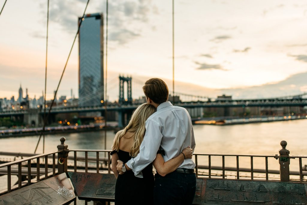 couple watching sunrise on Brooklyn bridge New York Engagement photographer
