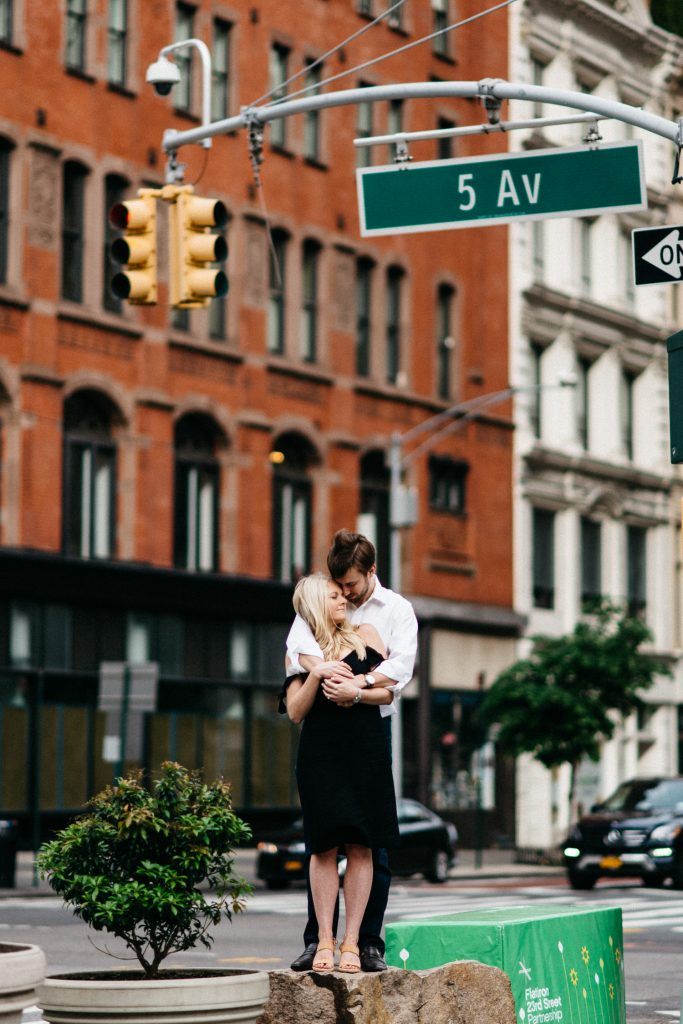couple hugging on top of a rock on 5th avenue New York Engagement photos