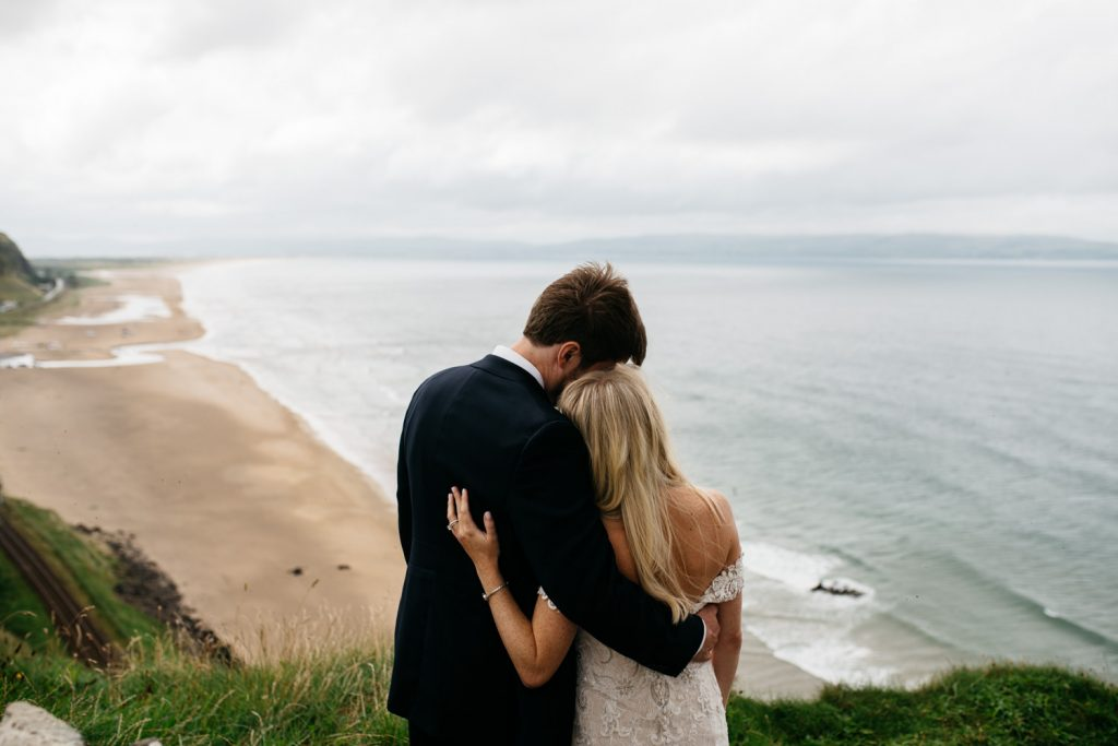bride and groom hugging into each other looking into the Atlantic Ocean Mussenden Temple Wedding