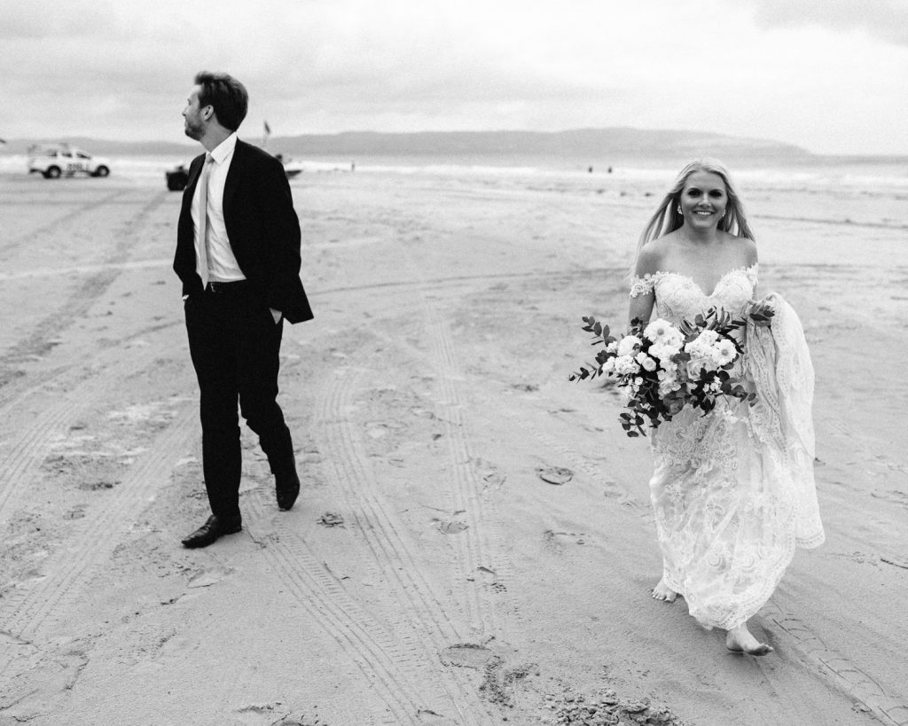 bride and groom walking on downhill beach  black and white  bride and groom dancing on downhill beach Mussenden Temple Wedding