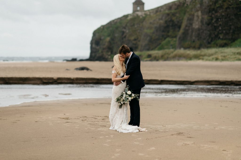 bride and groom hugging on the beach with Mussenden Temple in the background bride and groom dancing on downhill beach Mussenden Temple Wedding