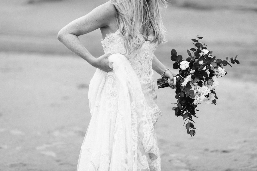 bride waling on the beach holding flowers black and white
