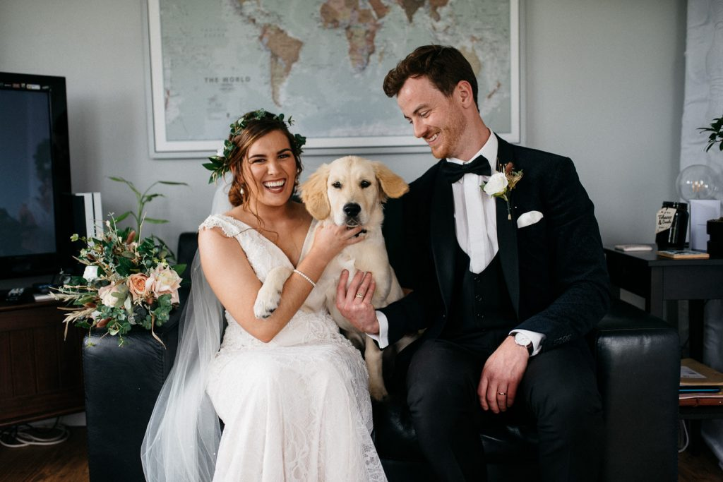 bride and groom laughing with dog wedding photographers Northern Ireland