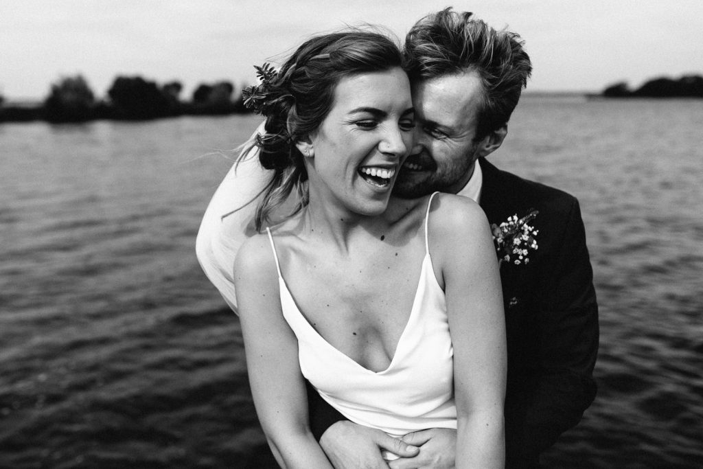 bride and groom laughing in front of the water black and white Gracehall Wedding Photography