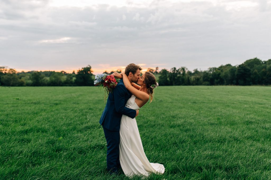 bride and groom kissing at sunset in a field Gracehall Wedding Photography