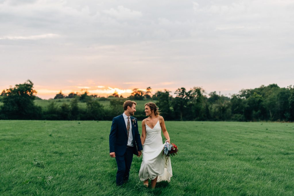 bride and groom walking and laughing at sunset Gracehall Wedding Photos