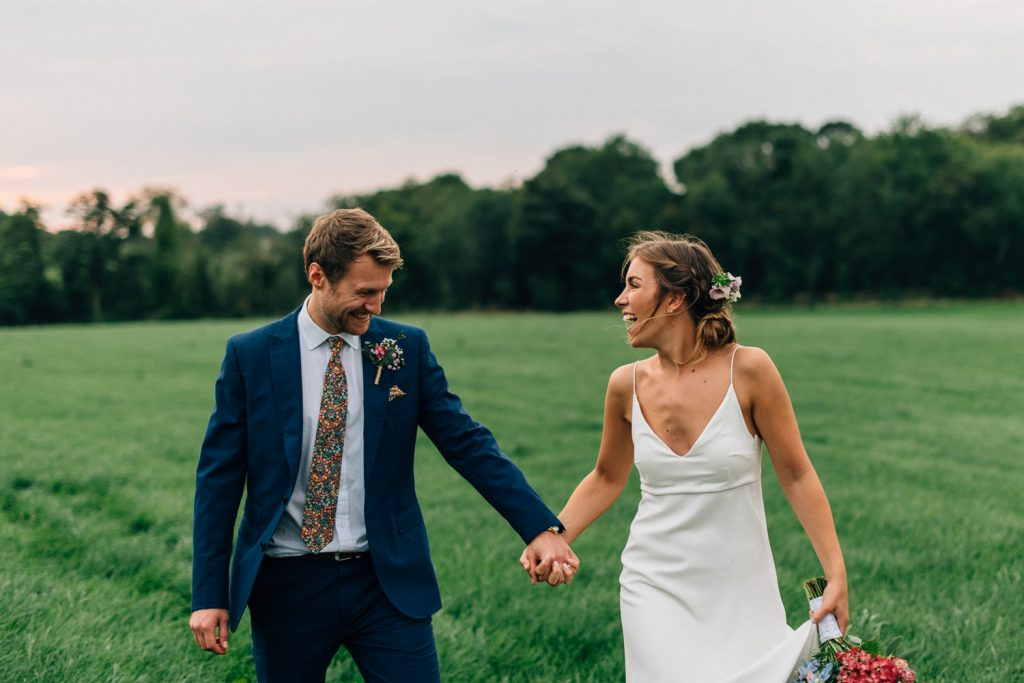 bride and groom holding hands laughing Gracehall Wedding Photos