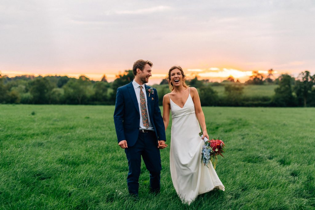 bride and groom laughing holding hands at sunset Gracehall Wedding Photography