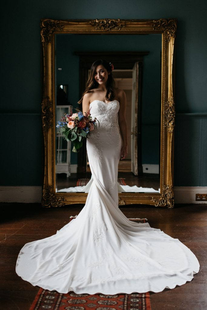 bride standing in front of the mirror holding her flowers Ivory Pavilion Wedding
