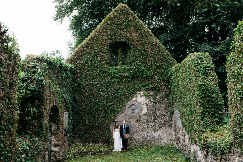 bride and groom holding hands in chapel ruins Ivory Pavilion Wedding