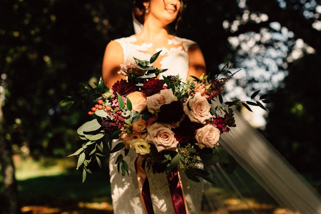 bride holing her flowers in the sun bride and groom dancing in the moon garden Drenagh House Estate Wedding Photography