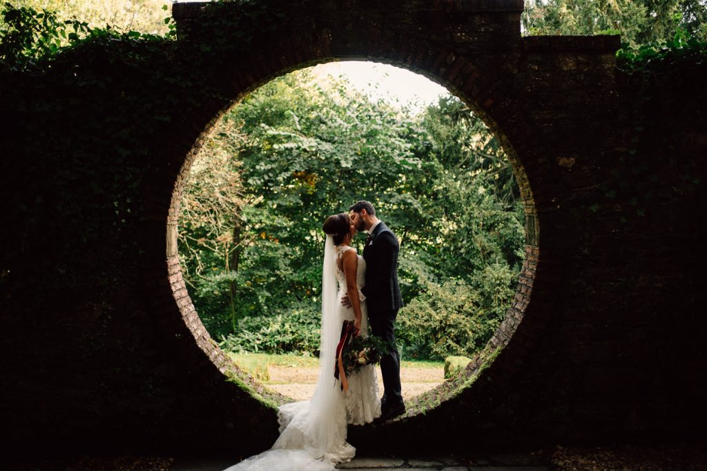 bride and groom kissing in brick circle bride and groom dancing in the moon garden Drenagh House Estate Wedding