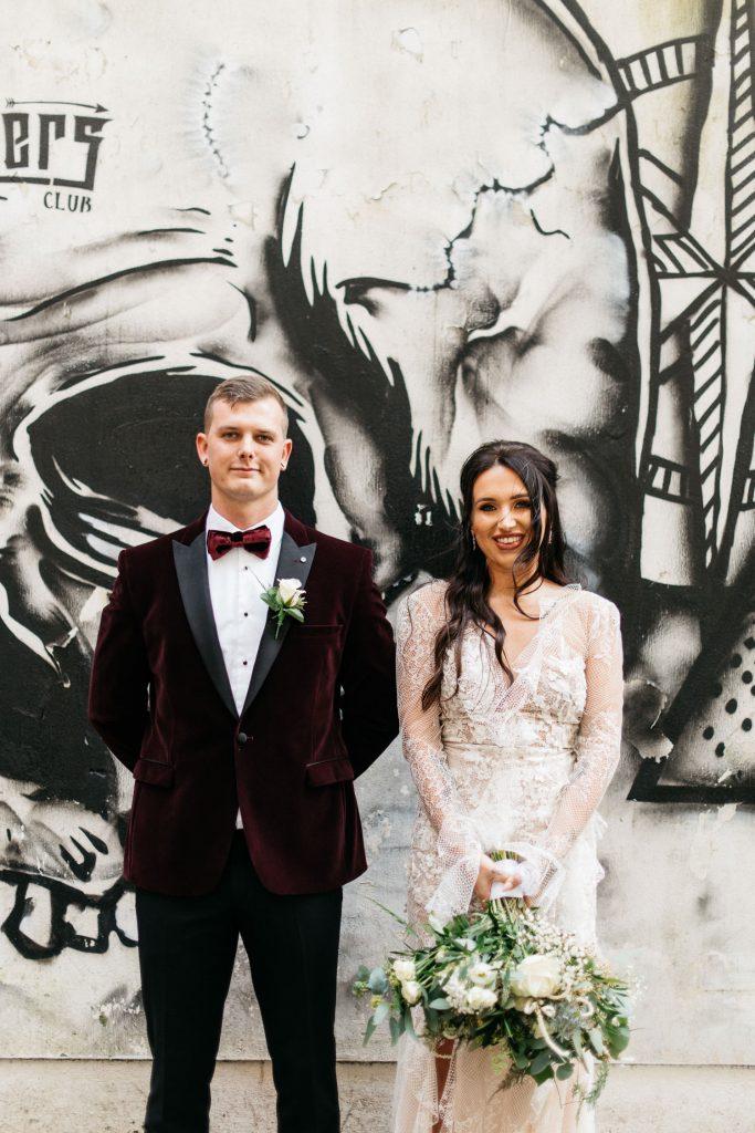 bride and groom in front of wall art Merchant Hotel Belfast Wedding
