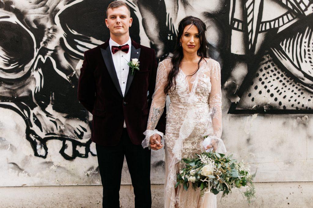 bride and groom standing in front of wall art Merchant Hotel Belfast Wedding Photos
