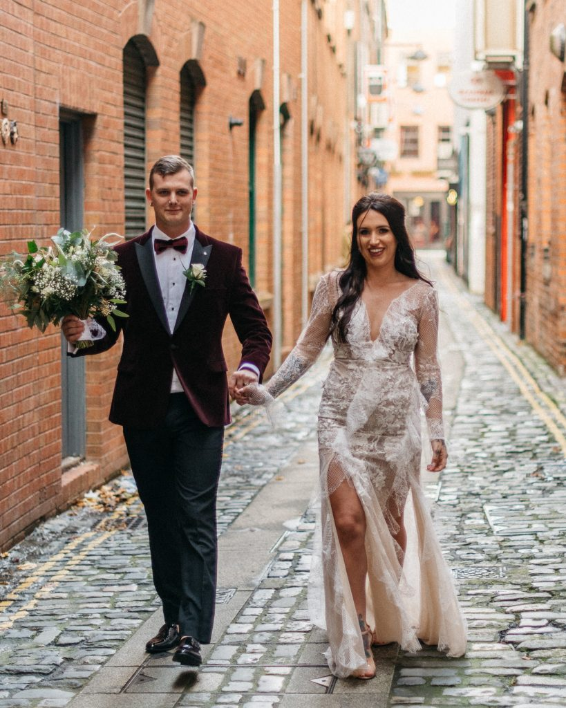 bride and groom walking on cobbled streets Merchant Hotel Belfast Wedding