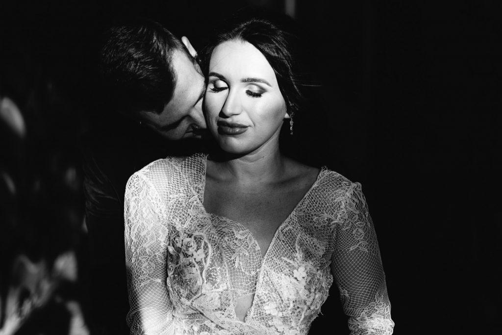 groom kissing bride in ally black and white Merchant Hotel Belfast Wedding