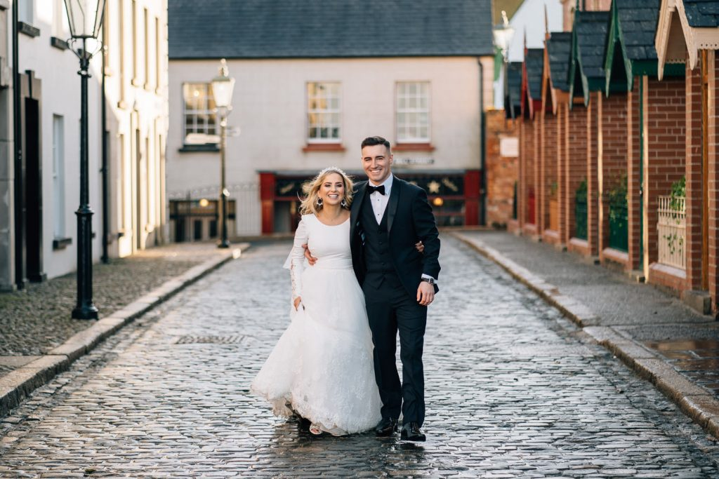 bride and groom waling on cobbled street at the folk museum Cultra Manor Wedding Photography