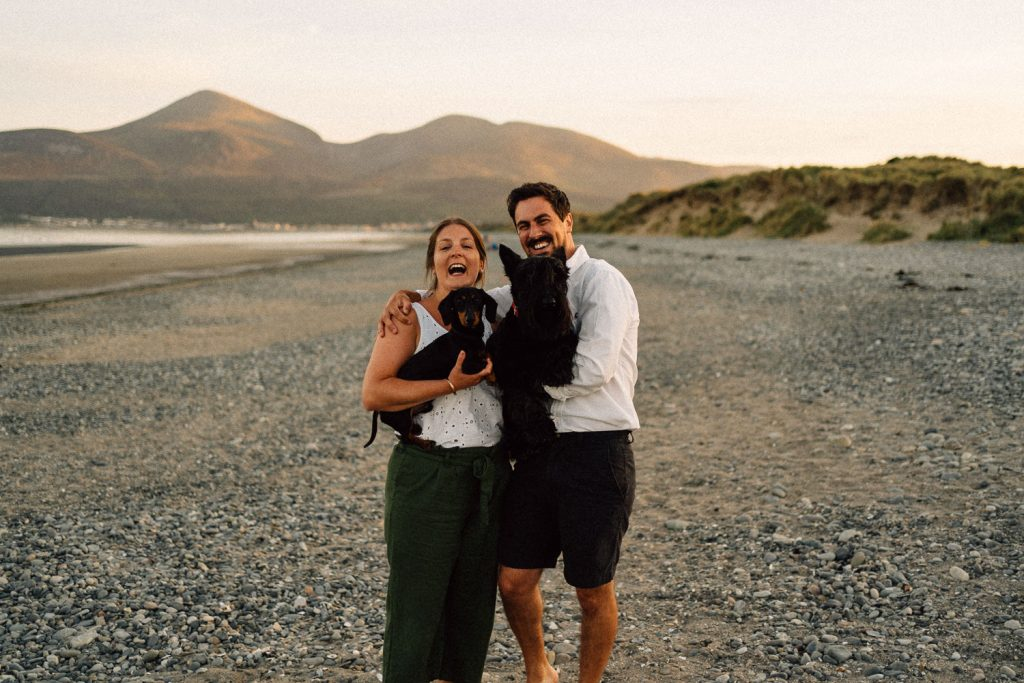 couple walking and laughing with dogs Engagement Photos Belfast