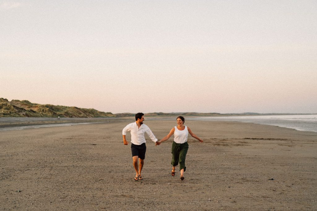 couple running on the beach Engagement Photos Belfast  Northern Ireland
