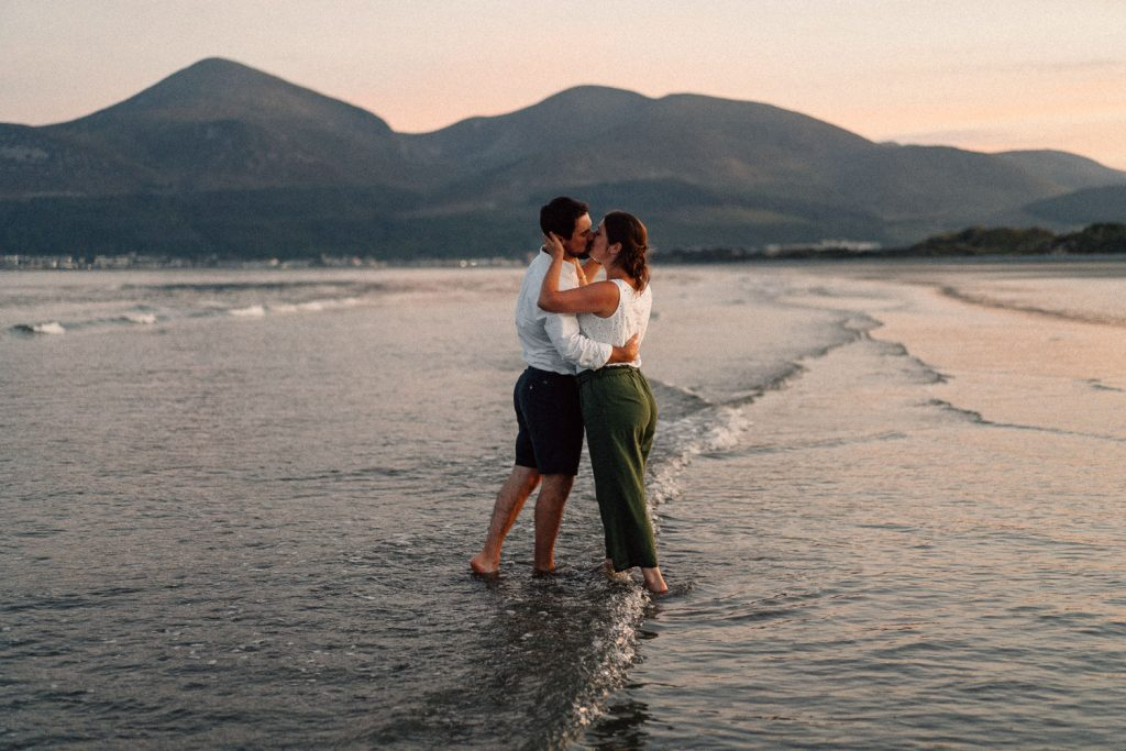couple kissing in the sea Mournes in the background Engagement Photos Belfast Northern Ireland
