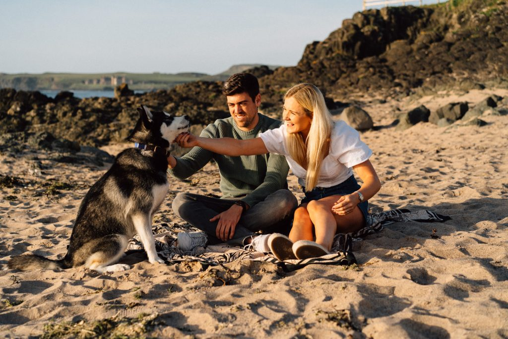 couple posing with husky don on their engagement shoot Northern Ireland Wedding & Engagement Photographer