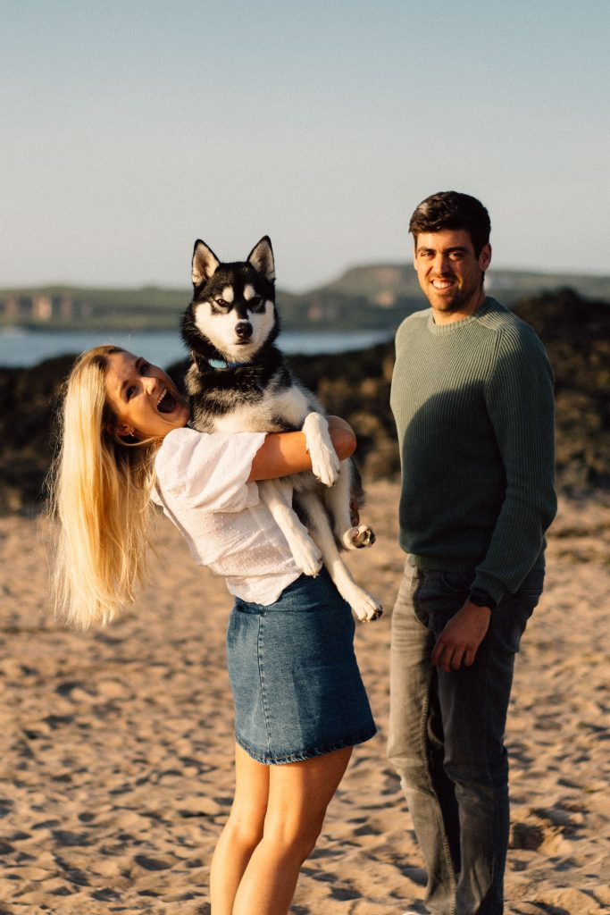 couple posing with husky don on their engagement shoot Northern Ireland Wedding & Engagement Photos