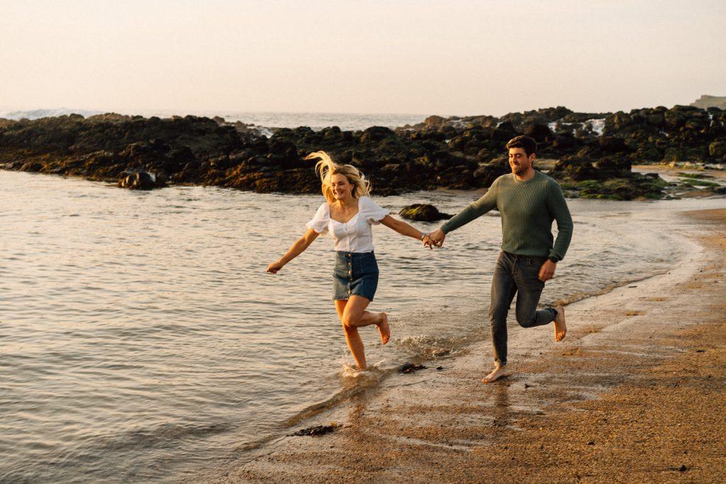 couple running on the beach north coast engagement  Northern Ireland Wedding & Engagement Photographer