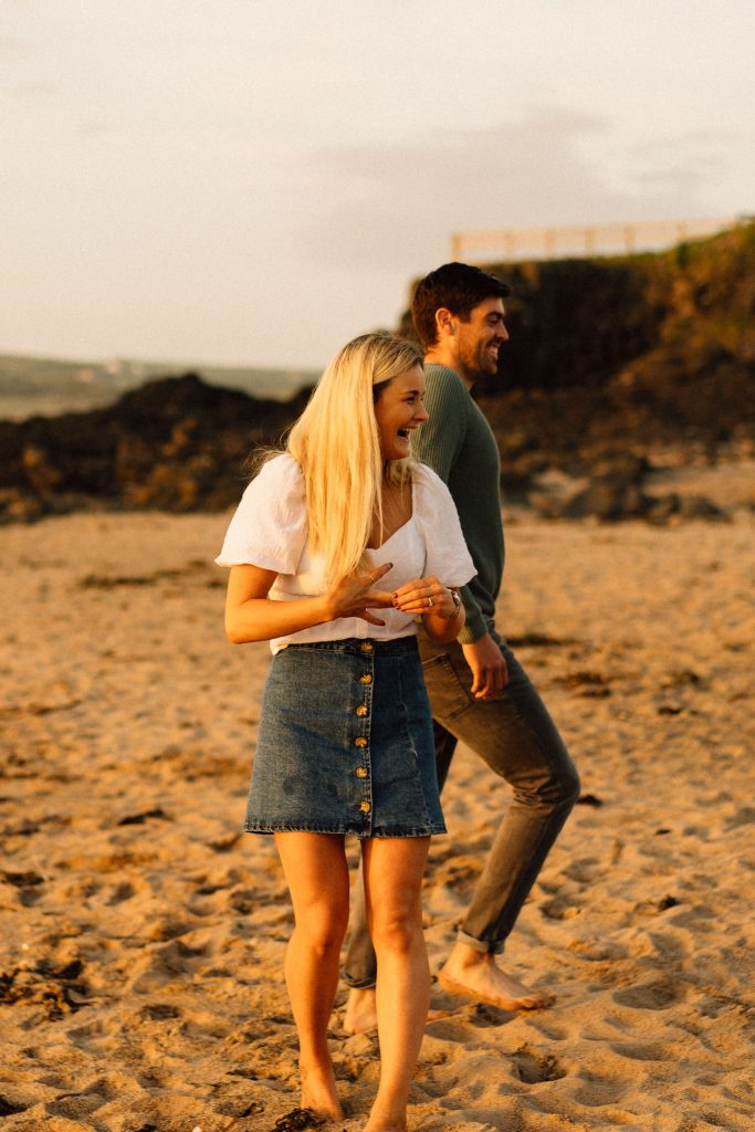 couple playing and laughing on the beach Northern Ireland Wedding & Engagement Photographer