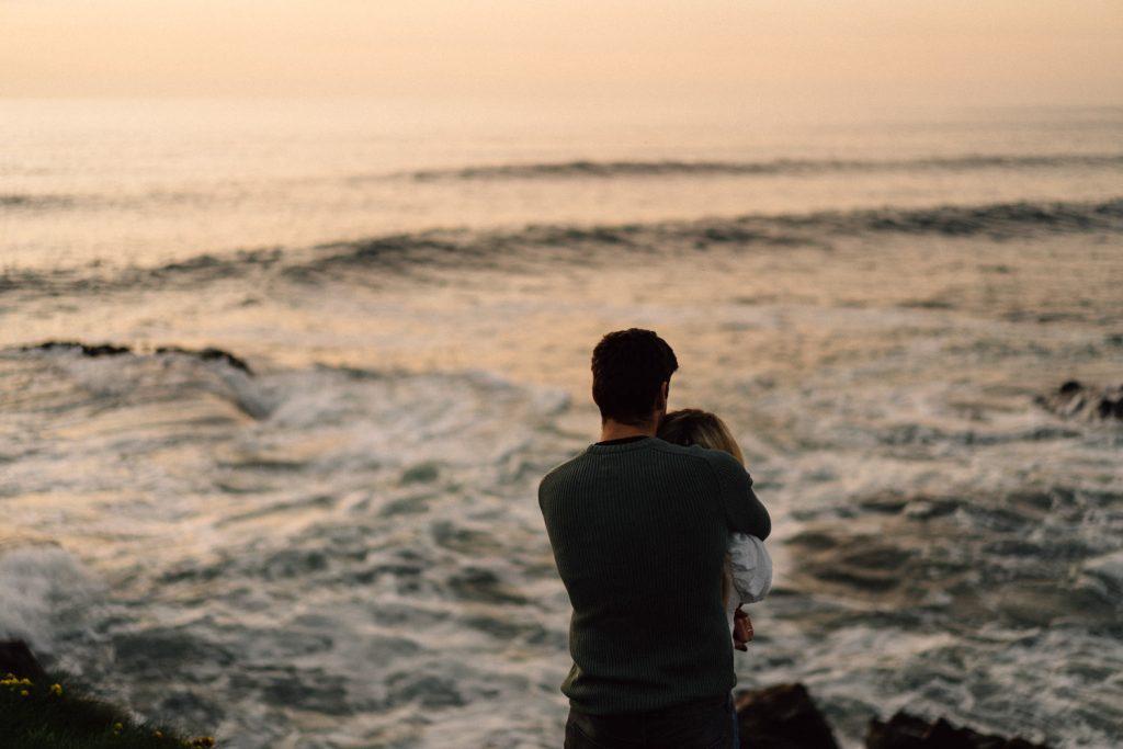 couple looking off into the Atlantic Ocean Northern Ireland Wedding & Engagement Photographer