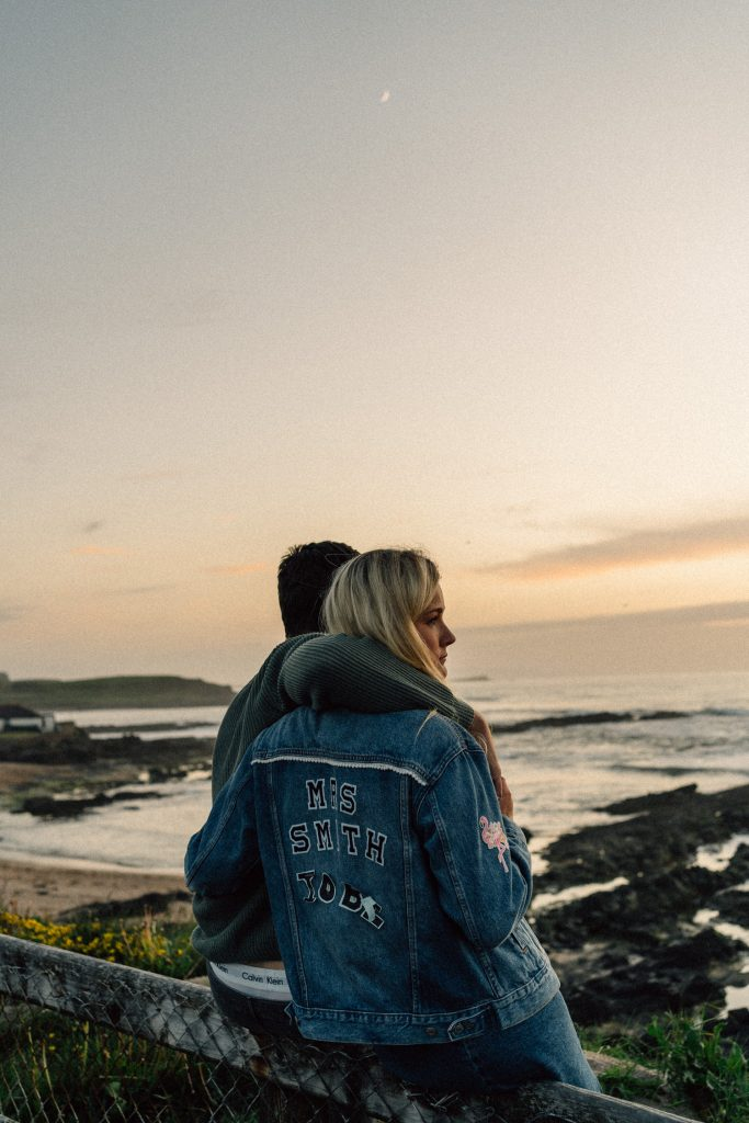 couple looking off into the sunset with moon visible Northern Ireland Wedding & Engagement Photos