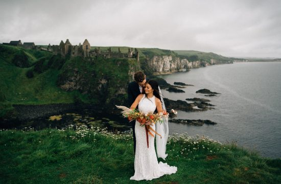 couple holding each other in front of Dunluce Castle Northern Ireland Elopement Photographer