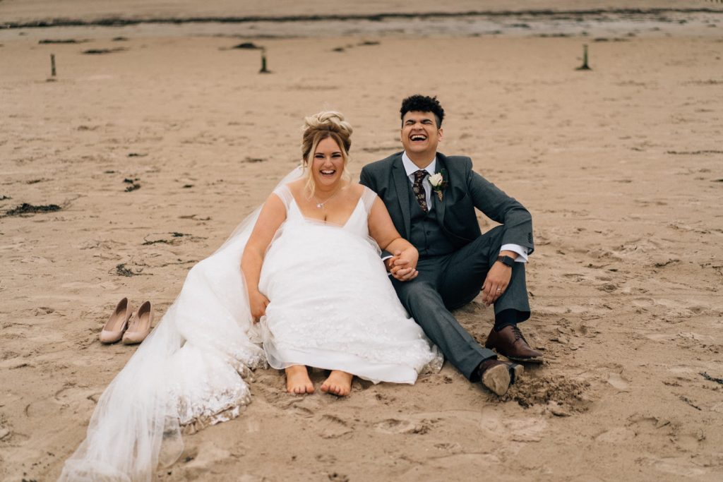 groom laughing wildy sitting on the beach Northern Ireland Elopement Photography