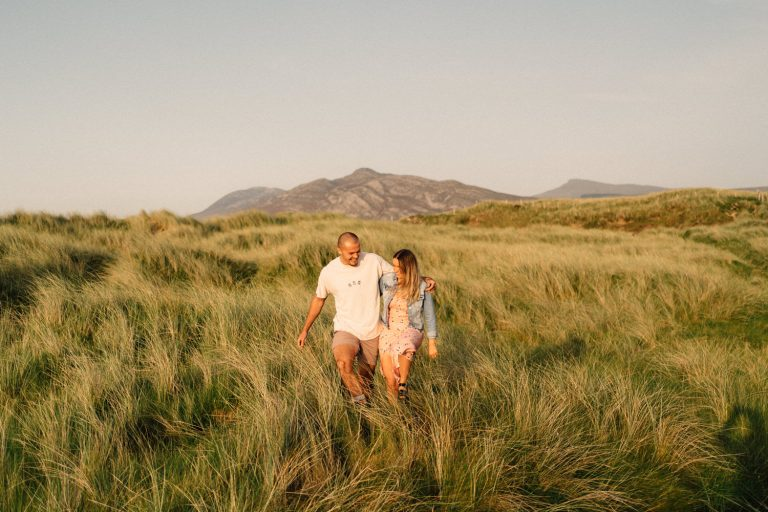 couple walking through the grass with mountains in the background on their engagement shoot Northern Ireland Wedding Photographer