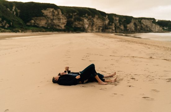 couple laying down on the sand at white park bay beach Elopement Photographer - Couples Photographer